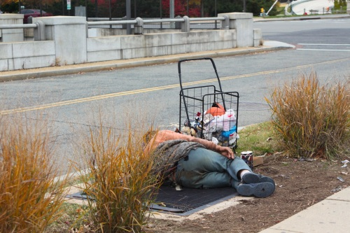 Sem-abrigo deitado na saída de ar quente. USA.
